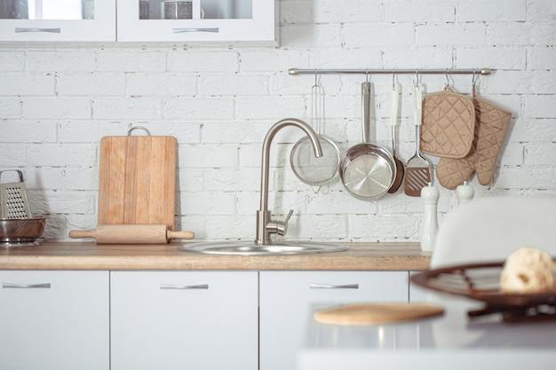 Modern stijlvol scandinavisch keukeninterieur met keukenaccessoires. helderwitte keuken met huishoudelijke artikelen. Gratis Foto