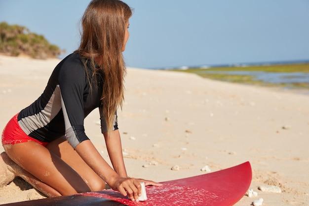 Moderne actieve sport, zomervakantie concept. horizontale weergave van actieve surfer gekleed in wetsuit Gratis Foto