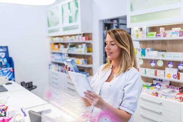 Moderne apotheker met digitale tablet die naar producten in gegevensbestand zoekt. Premium Foto