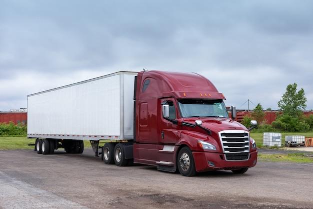 Moderne big rig semi-vrachtwagen voor lang transport met een hoge cabine voor het verbeteren van de aerodynamische eigenschappen die een droge bestelwagen-oplegger vervoert met commerciële lading over de weg. Premium Foto