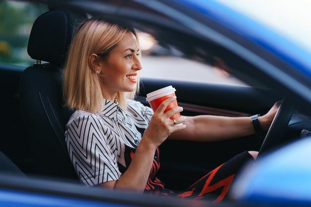 Moderne blonde vrouw met een kopje koffie tijdens het rijden in de stad Gratis Foto