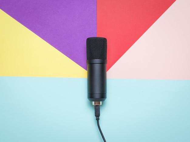 Moderne condensatormicrofoon op een oppervlak van vijf kleuren Premium Foto