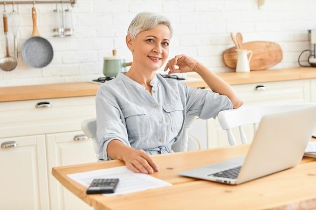 Moderne energieke zakenvrouw van volwassen leeftijd zittend aan de eettafel ontbijten en e-mail controleren met behulp van draagbare computer. stijlvolle senior vrouwelijke freelancer thuiswerken op laptop Gratis Foto