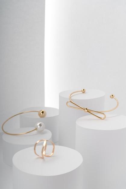 Moderne gouden armbanden en gouden ring op witte ronde platforms Premium Foto