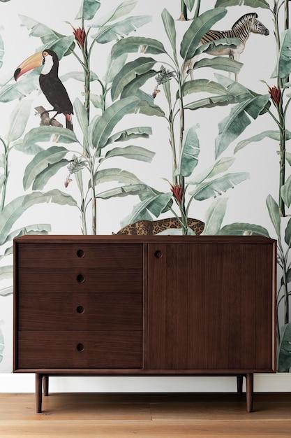 Moderne houten kast uit het midden van de eeuw door een lommerrijke muur Gratis Foto