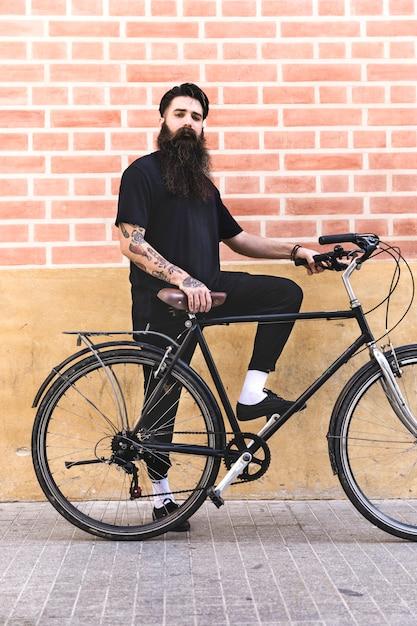 Moderne jonge mens die zich met zijn fiets tegen bakstenen muur bevindt Gratis Foto