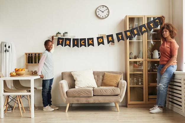 Moderne jonge moeder en haar zoon hangende slinger met trick or treat-letters op de muur voor halloween-feest Premium Foto