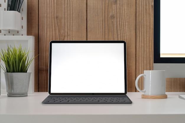 Moderne kantoorwerkplek met het lege model van de het schermtablet, pc en modieuze levering Premium Foto