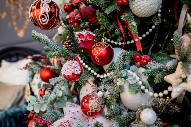 Moderne kerstboom, versierd met vintage ornamenten, ratan ballen, jute en tartan linten, houten sneeuwvlokken, rode bessen en ballen, rode witte ballen. kerstballen. Premium Foto