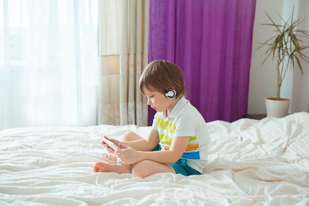 Moderne klein kind zittend op bed met smartphone in zijn handen Premium Foto