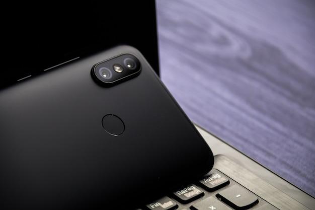 Moderne laptop en smartphone kopie ruimte. mobiel met dubbele camera en vingerafdruklezer Premium Foto