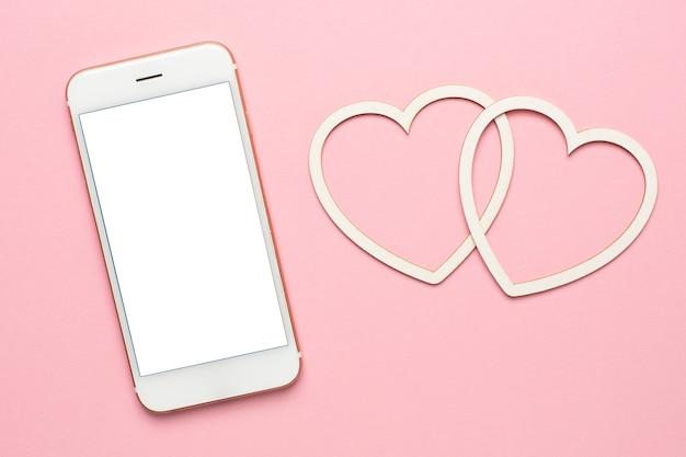 Moderne mobiele telefoon met hartjes, sociaal afstand en dating concept, valentijnsdag mock up, kopie ruimte op display bovenaanzicht Premium Foto