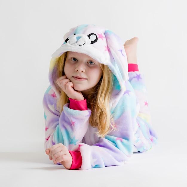 Moderne mode - mooie blonde meisje die zich voordeed op een witte achtergrond in kigurumi-pyjama, konijntjeskostuum Premium Foto