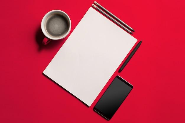 Moderne rode bureau tafel met smartphone en kopje koffie. Gratis Foto