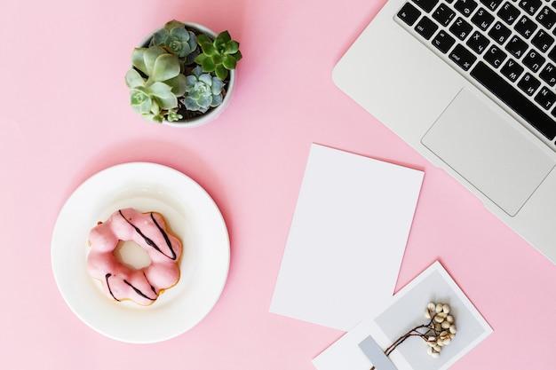 Moderne roze bureaulijst met laptop, succulente bloem, doughnut en document spatie voor tekst. Premium Foto