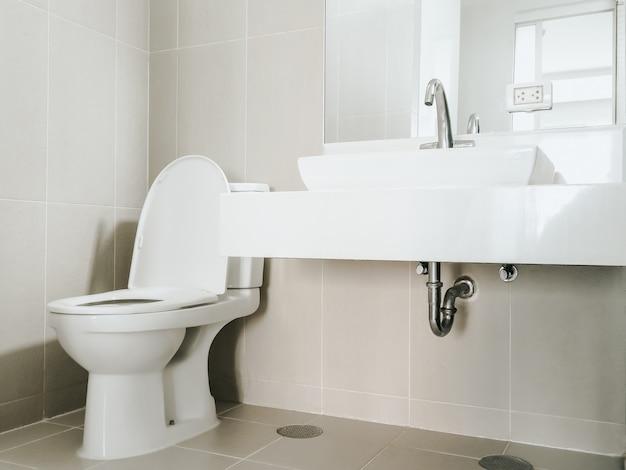 Moderne rvs kraan op wastafel in de badkamer bij de spiegel aan de muur en doorspoeltoilet op de hoek Premium Foto