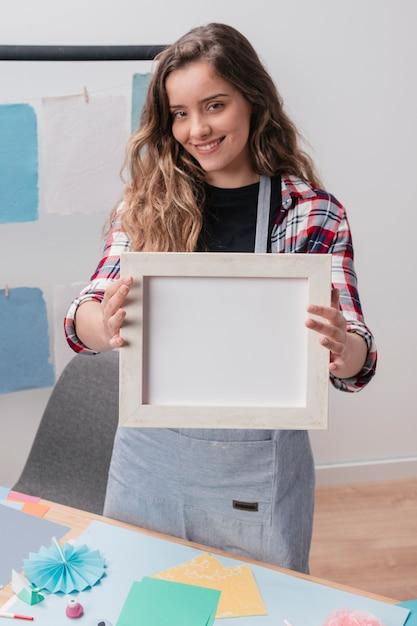 Moderne vrouw die wit leeg frame toont Gratis Foto