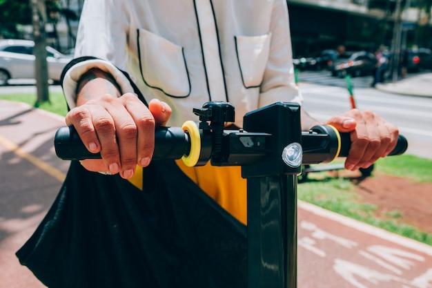 Moderne vrouw in een stad met een elektrische autoped Gratis Foto