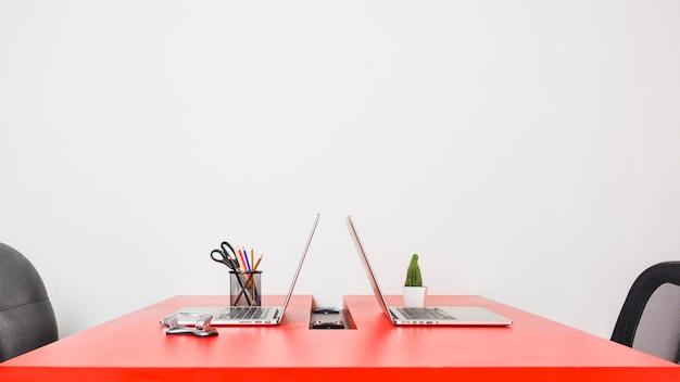 Moderne werkplaats met twee laptops op rode lijst tegen witte muur Gratis Foto