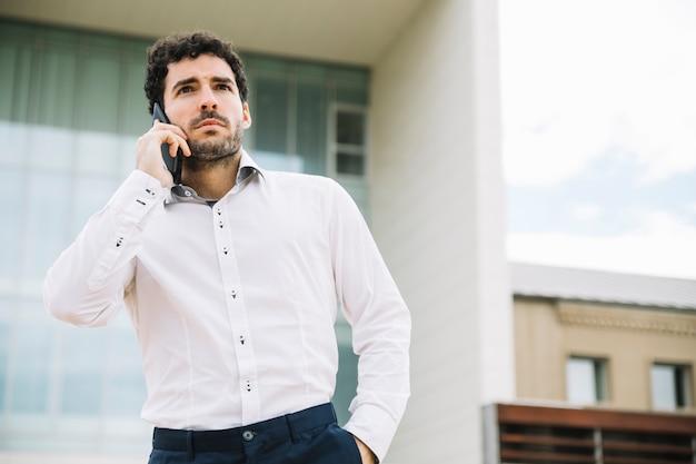 Moderne zakenman die telefoongesprek in openlucht maakt Gratis Foto