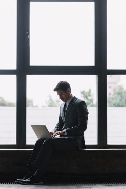 Moderne zakenman met laptop op zijn schoot zitten voor raam Gratis Foto
