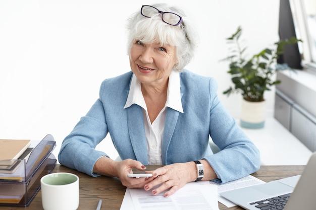 Moderne zelfverzekerde vrouw van middelbare leeftijd van in de zestig met een kleine pauze, zittend op haar werkplek, nieuws controleren of scrollen op sociale media via mobiele telefoon, koffie drinken en kijken met een glimlach Gratis Foto