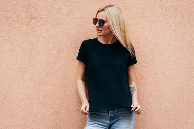 Modieus blondemeisje die zwarte t-shirt dragen en glazen die tegen muur stellen Premium Foto