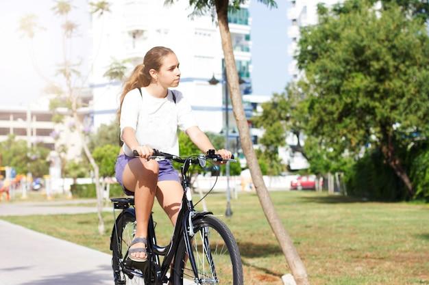 Modieus jong tienermeisje in korte broek en t-shirt rijdt op een fiets in een zomerpark Premium Foto