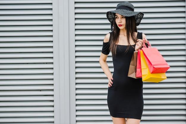 Modieus meisje bedrijf boodschappentassen staan Gratis Foto