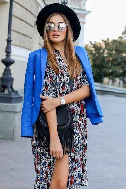 Modieus meisje in elegante herfst outfit wandelen tijdens vakantie in europa. stijlvolle leren tas. blauw jasje en zwarte hoed. Gratis Foto