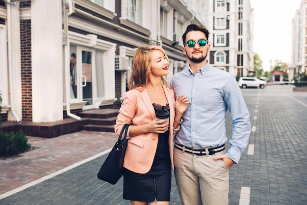 Modieus paar loopt op straat in de stad. knappe bebaarde man in zonnebril is meisje knuffelen en kijkt ver weg. Gratis Foto