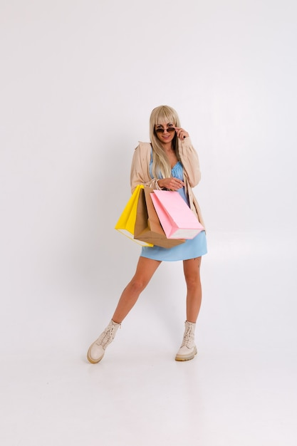 Modieus portret van een slanke blonde met lang haar in een lichtblauwe jurk en een corduroy overhemd Gratis Foto