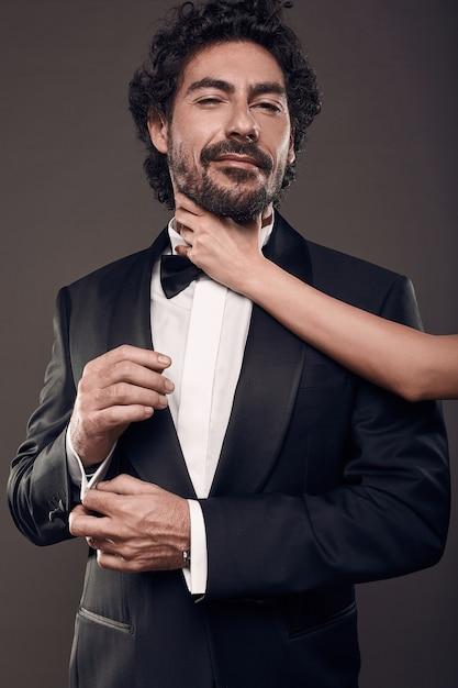 Modieus portret van elegant sexy paar in studio. brutale man in pak met vrouw hand aanraken van zijn gezicht op donkere achtergrond Gratis Foto