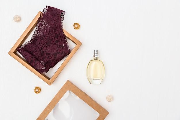 Modieus vrouwelijk ondergoed, kastanjebruin damesslipje in geschenkverpakking, glazen fles met parfum. Premium Foto