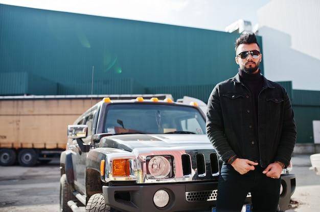 Modieuze bebaarde jonge man poseren buitenshuis met grote auto Premium Foto