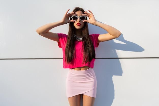 Modieuze brunette vrouw in zomerkleding en zonnebril poseren over witte stedelijke muur. Gratis Foto