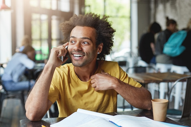 Modieuze donkere man met krullend haar draagt een geel t-shirt omringd met boeken die rust hebben in een gezellige cafetaria, koffie drinken en praten via mobiel Gratis Foto