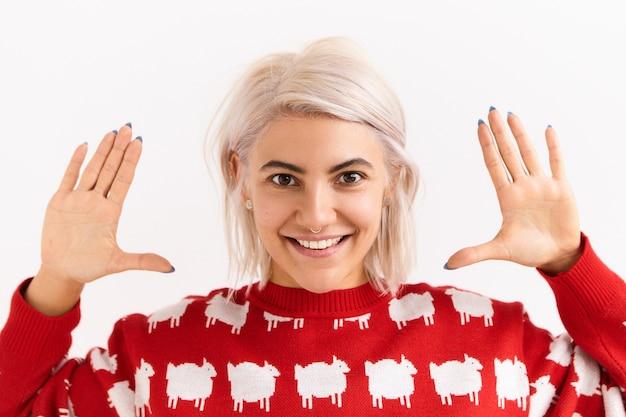 Modieuze emotionele jonge vrouw met geverfd roze haar poseren geïsoleerd gebaar maken, hand in hand op haar gezicht, opgewonden gelaatsuitdrukking. jeugd, plezier en positieve emoties Gratis Foto