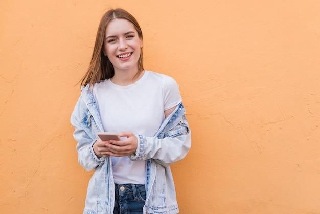 Modieuze gelukkige cellphone die van de vrouwenholding camera bekijken die zich dichtbij beige muur bevinden Gratis Foto