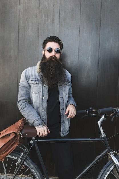 Modieuze jonge bebaarde man permanent met fiets voor zwarte houten muur Gratis Foto