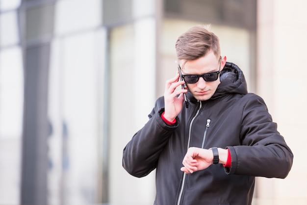 Modieuze jonge mens die op mobiele telefoon spreekt die tijd op zijn polshorloge bekijkt Gratis Foto