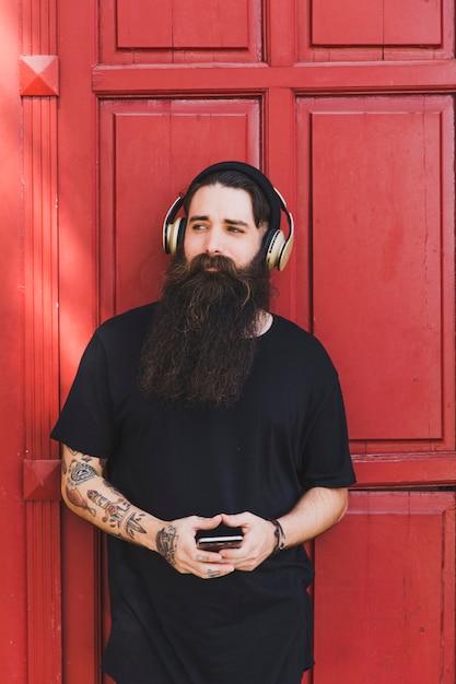 Modieuze jonge mens het luisteren muziek op hoofdtelefoons tegen rode deur Gratis Foto