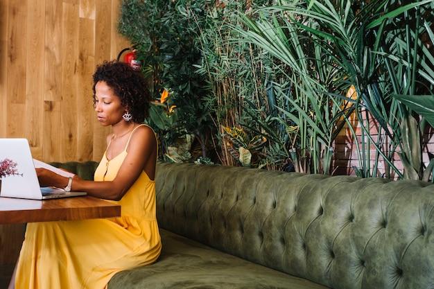 Modieuze jonge vrouw die documenten met laptop op houten lijst in het restaurant bekijken Gratis Foto