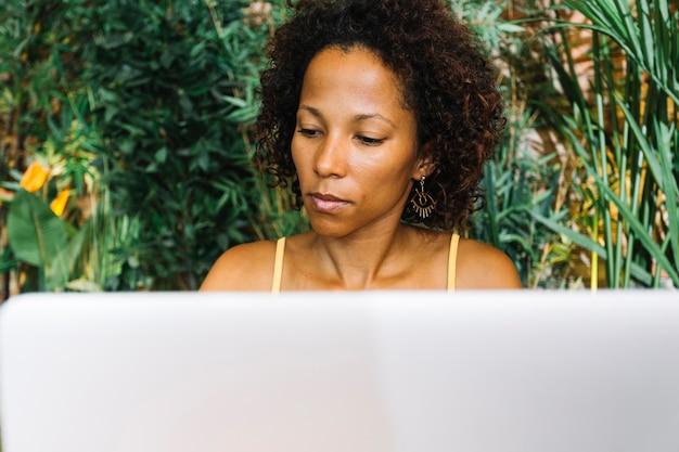 Modieuze jonge vrouw die laptop bekijkt Gratis Foto