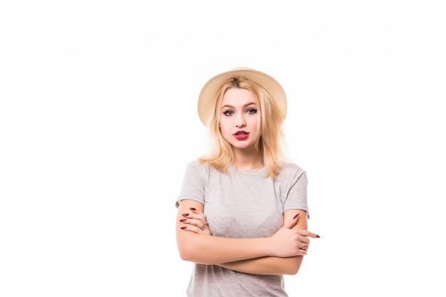 Modieuze jonge vrouw in hoed die zich met gevouwen wapens bevinden die op de witte muur worden geïsoleerd Gratis Foto