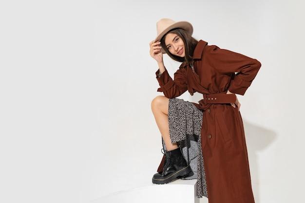 Modieuze jonge vrouw in hoed en trendy winterjas poseren Gratis Foto