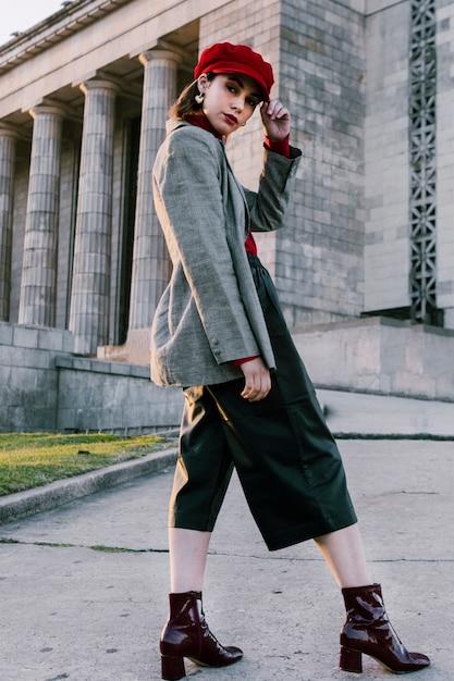 Modieuze jonge vrouw met hand op haar rode dop camera kijken Gratis Foto