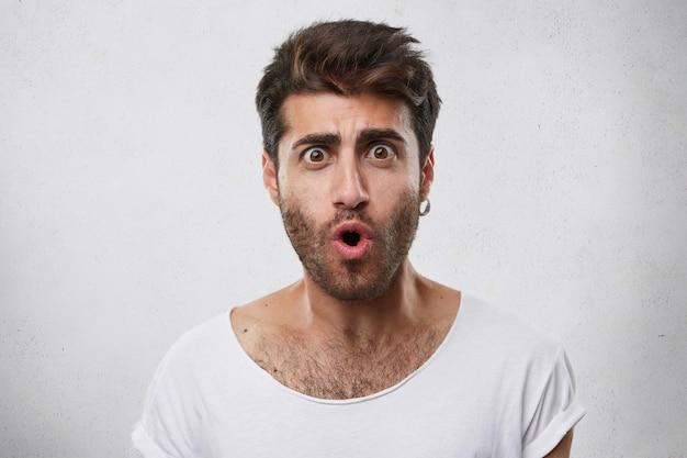 Modieuze knappe man met baard dragen oorbel en wit t-shirt kijken met wijd geopende ogen en mond uiting van zijn verrassing en schok Gratis Foto