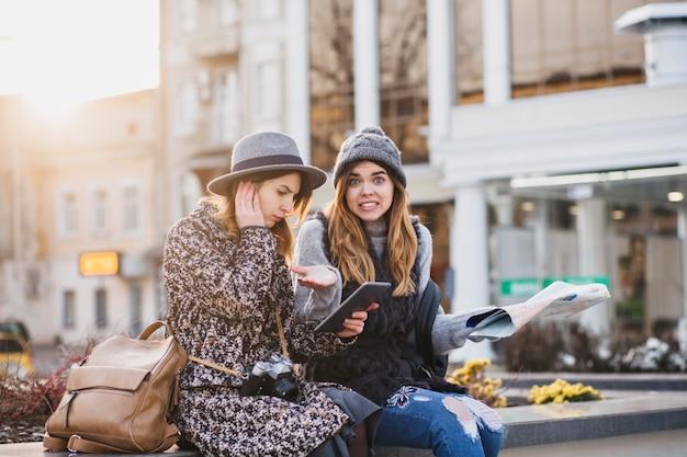 Modieuze lachende vrouwen die in het centrum van de stad zitten en heldere emoties uitdrukken op een zonnige dag in de stad. gelukkig samen reizen, proberen de locatie op de kaart te vinden. Gratis Foto