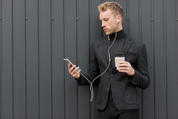 Modieuze man met koffie smartphone kijken Gratis Foto